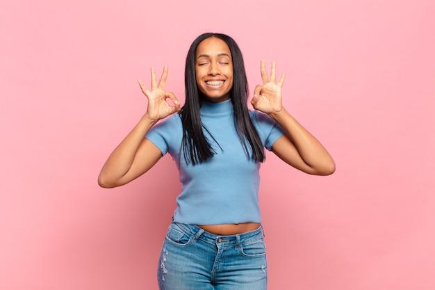 Giovane donna di colore che sembra concentrata e medita, si sente soddisfatta e rilassata, pensa o fa una scelta