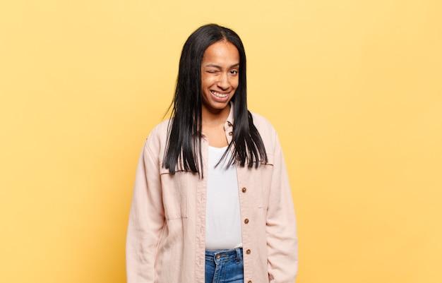 Giovane donna di colore che sembra felice e amichevole, sorride e ti fa l'occhiolino con un atteggiamento positivo