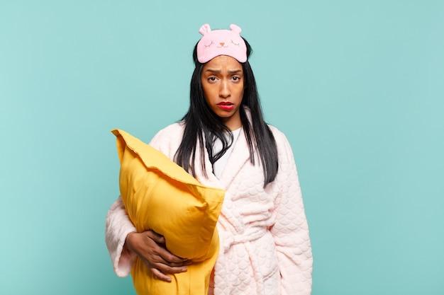 Giovane donna di colore che sembra perplessa e confusa, mordendosi il labbro con un gesto nervoso, non conoscendo la risposta al problema. concetto di pigiama