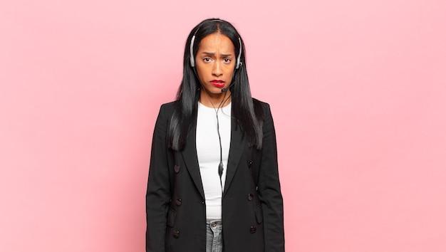 Giovane donna di colore che sembra perplessa e confusa, mordendosi il labbro con un gesto nervoso, non conoscendo la risposta al problema. concetto di telemarketing