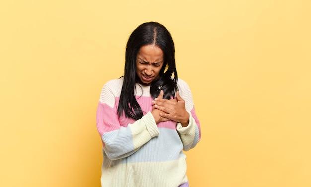 Giovane donna di colore che sembra triste, ferita e con il cuore spezzato, tenendo entrambe le mani vicino al cuore, piangendo e sentendosi depressa