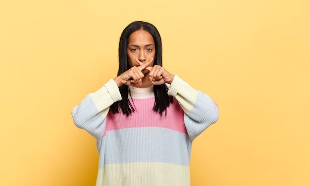Giovane donna di colore che sembra seria e dispiaciuta con entrambe le dita incrociate davanti in segno di rifiuto, chiedendo silenzio