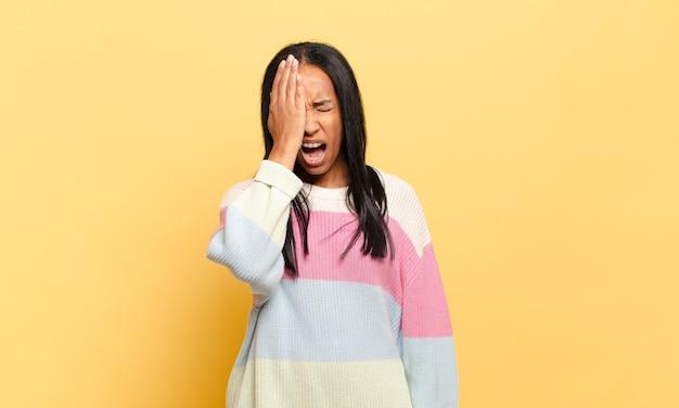 Giovane donna di colore che sembra assonnata, annoiata e sbadigliante, con mal di testa e una mano che copre metà del viso