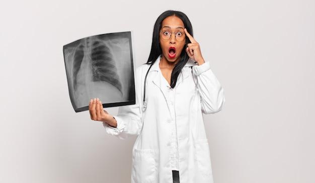 Giovane donna di colore che sembra sorpresa, a bocca aperta, scioccata, realizzando un nuovo pensiero, idea o concetto. concetto di medico
