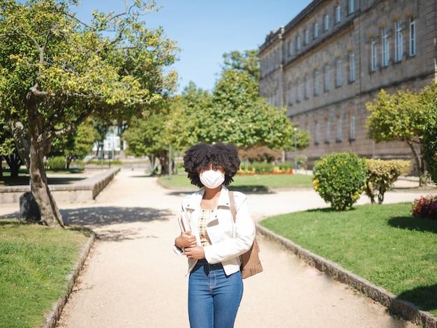 Giovane donna di colore all'esterno, con in mano alcuni libri e indossa una maschera protettiva