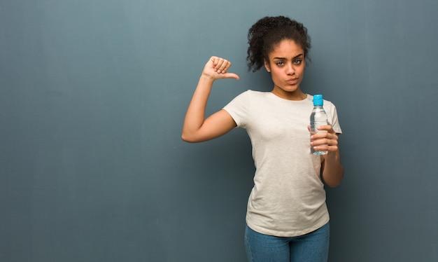 Giovane donna di colore che punta le dita, esempio da seguire. tiene in mano una bottiglia d'acqua.