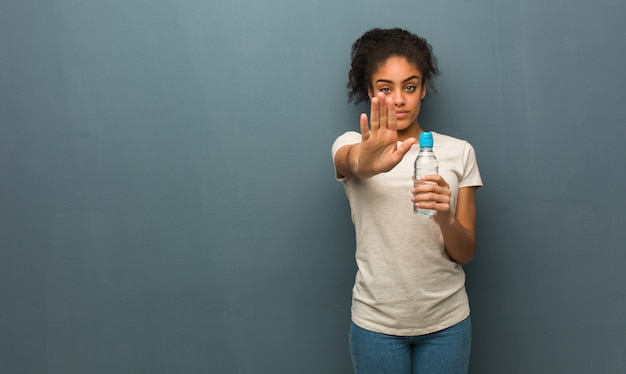 Giovane donna di colore che mette la mano nella parte anteriore. tiene in mano una bottiglia d'acqua.