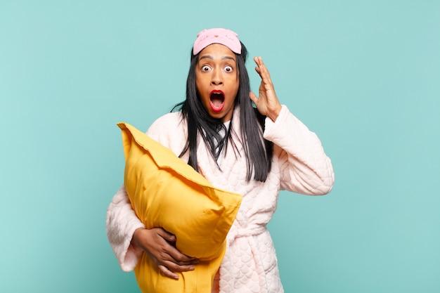 Giovane donna di colore che urla con le mani in aria, sentendosi furiosa, frustrata, stressata e turbata. concetto di pigiama