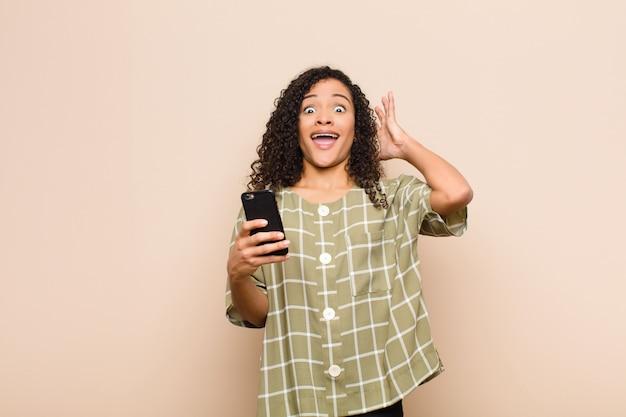 Giovane donna di colore che grida con le mani in alto nell'aria, sentendosi furioso, frustrato, stressato e arrabbiato con uno smartphone