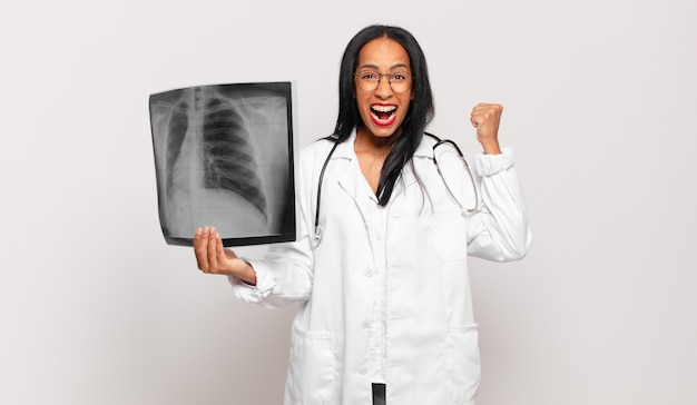 Giovane donna di colore che grida in modo aggressivo con un'espressione arrabbiata o con i pugni chiusi celebrando il successo. concetto di medico