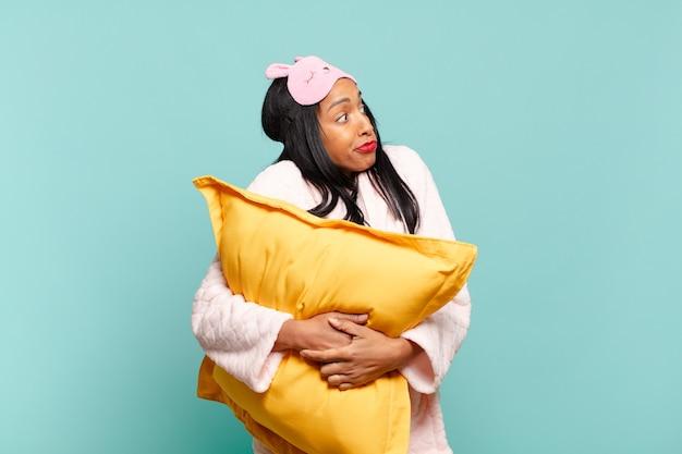 Giovane donna di colore che scrolla le spalle, sentendosi confusa e incerta, dubbiosa con le braccia incrociate e lo sguardo perplesso. concetto di pigiama