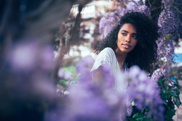 Giovane seduta della donna di colore circondata dai fiori