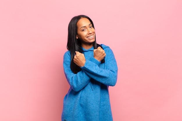 Giovane donna di colore che sorride allegramente e festeggia, con i pugni serrati e le braccia incrociate, sentendosi felice e positiva
