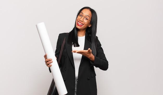 Giovane donna di colore che sorride allegramente, si sente felice e mostra un concetto nello spazio della copia con il palmo della mano. concetto di architetto