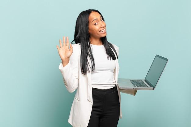 Giovane donna di colore che sorride allegramente e allegramente, agitando la mano, accogliendoti e salutandoti, o salutandoti. concetto di laptop
