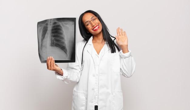 Giovane donna di colore che sorride allegramente e allegramente, agitando la mano, accogliendoti e salutandoti, o salutandoti. concetto di medico