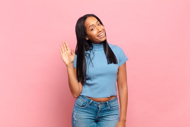 Giovane donna di colore che sorride allegramente e allegramente, agitando la mano, accogliendoti e salutandoti, o salutandoti