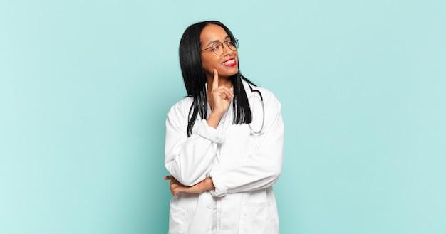 Giovane donna di colore che sorride felicemente e sogna ad occhi aperti o dubita, guardando di lato. concetto di medico