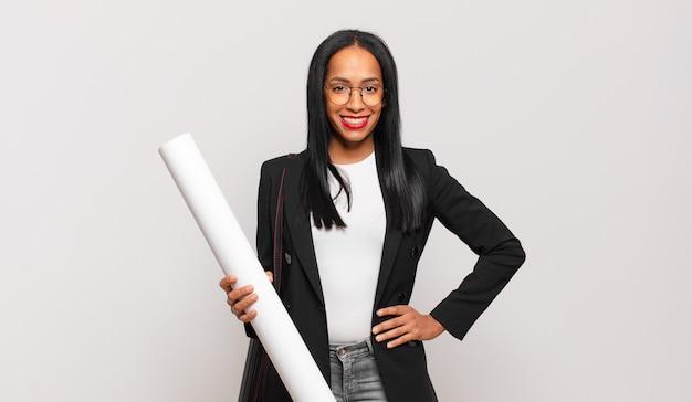 Giovane donna di colore che sorride felicemente con una mano sull'anca e un atteggiamento fiducioso, positivo, orgoglioso e amichevole. concetto di architetto