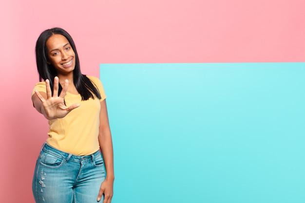 Giovane donna di colore sorridente e dall'aspetto amichevole, mostrando il numero cinque o il quinto con la mano in avanti, conto alla rovescia. copia il concetto di spazio