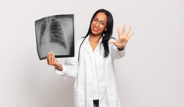 Giovane donna di colore sorridente e dall'aspetto amichevole, mostrando il numero cinque o il quinto con la mano in avanti, conto alla rovescia. concetto di medico