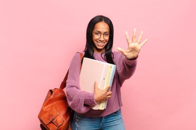 Giovane donna di colore che sorride e sembra amichevole, mostrando il numero cinque o quinto con la mano in avanti, contando alla rovescia. concetto di studente