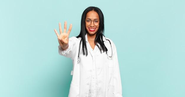 Giovane donna di colore sorridente e dall'aspetto amichevole, mostrando il numero quattro o il quarto con la mano in avanti, conto alla rovescia. concetto di medico