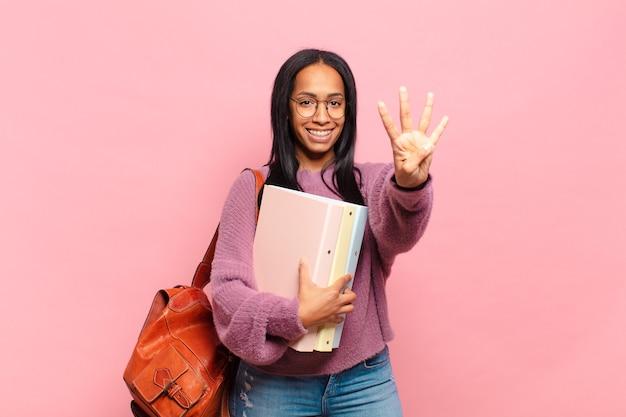 Giovane donna di colore sorridente e dall'aspetto amichevole, mostrando il numero quattro o il quarto con la mano in avanti, conto alla rovescia. concetto di studente
