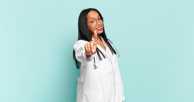 Giovane donna di colore che sorride con orgoglio e sicurezza facendo la posa numero uno in modo trionfante, sentendosi come un leader. concetto di medico