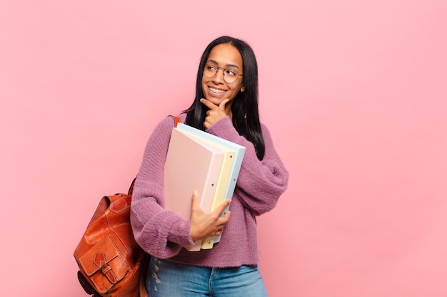 Giovane donna di colore che sorride con un'espressione felice e sicura con la mano sul mento, chiedendosi e guardando di lato. concetto di studente