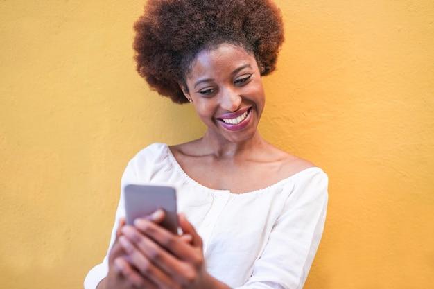 Giovane donna di colore che sta isolata sopra giallo facendo uso del telefono cellulare astuto