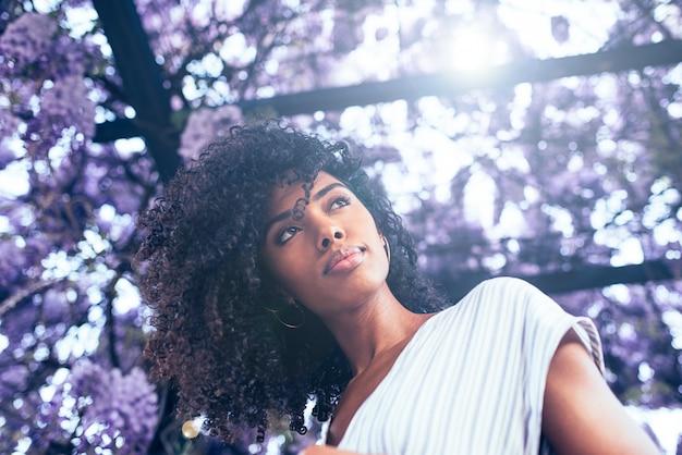 Giovane donna di colore circondata da fiori