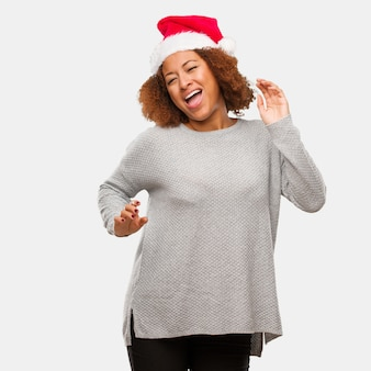 Giovane donna nera che indossa un cappello santa ballando e divertendosi