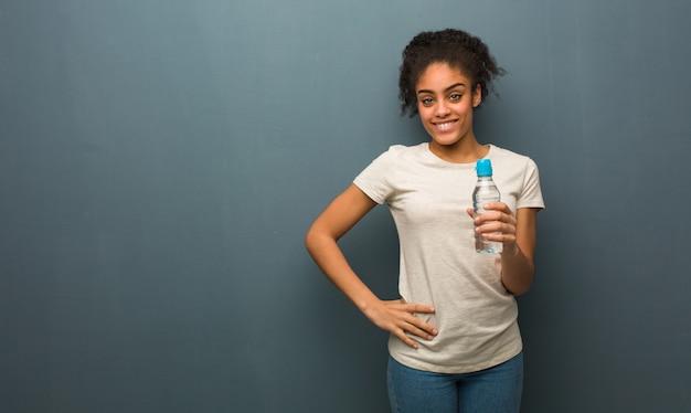 Giovane donna di colore con le mani sui fianchi. tiene in mano una bottiglia d'acqua.