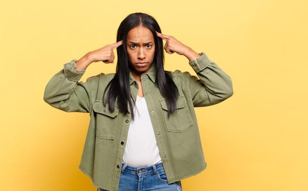 Giovane donna di colore con uno sguardo serio e concentrato, brainstorming e pensando a un problema impegnativo