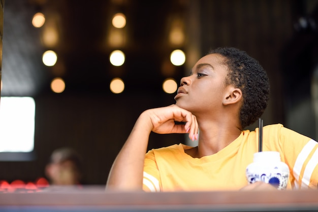 Giovane donna di colore con i capelli molto corti prendendo un bicchiere di tè freddo.