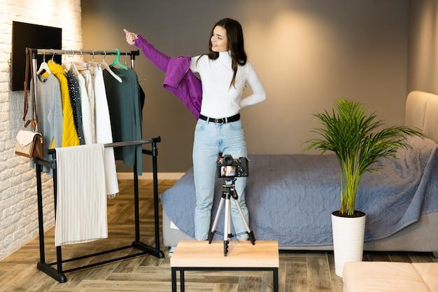 Giovane ragazza blogger con i capelli scuri mostra i suoi vestiti ai suoi follower sui social media per venderli in negozio online