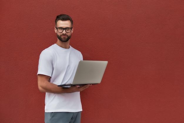 Giovane blogger bel giovane in abiti casual e occhiali con laptop e guardando