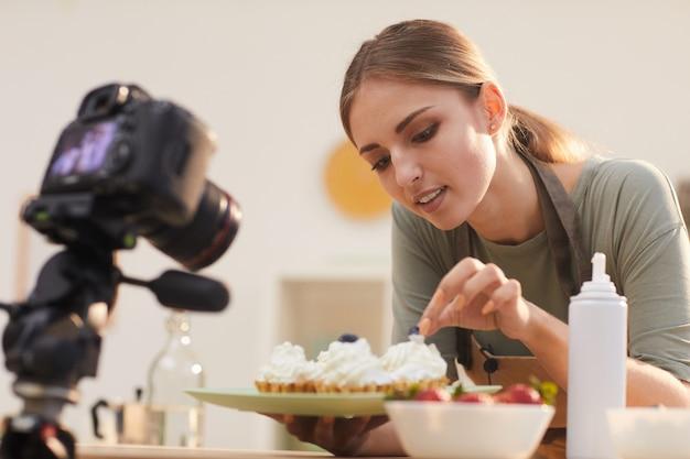 Giovane blogger che mostra il processo di decorazione delle torte da forno e lo riprende nel video