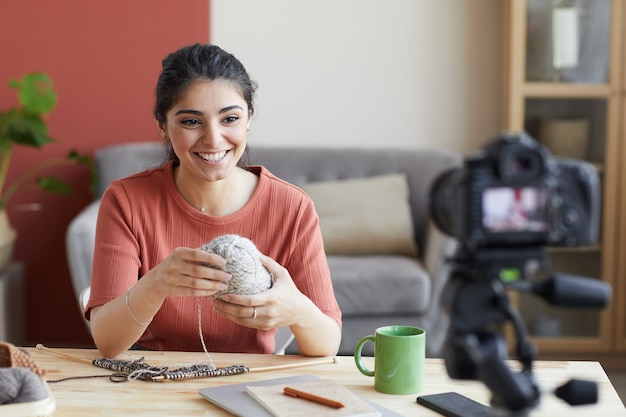 Giovane blogger sorridendo davanti mentre è seduta al tavolo lei insegna le lezioni di maglia online