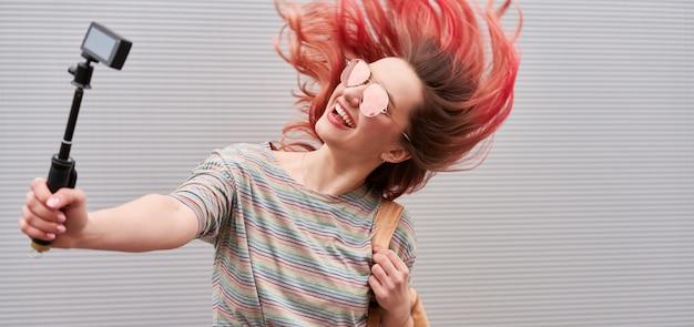 Giovane donna blogger con i capelli volanti tinti di rosa che ballano vicino al muro grigio e fanno vlog con la action cam