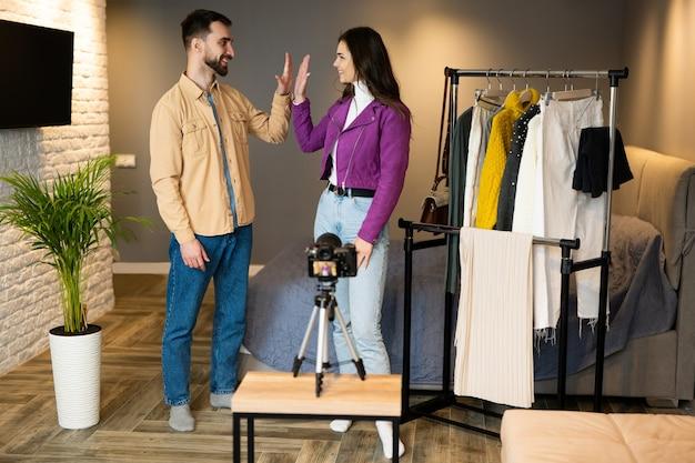 I giovani blogger hanno finito di filmare il loro vlog al chiuso sulla vendita di vestiti e darsi cinque a vicenda per un buon lavoro