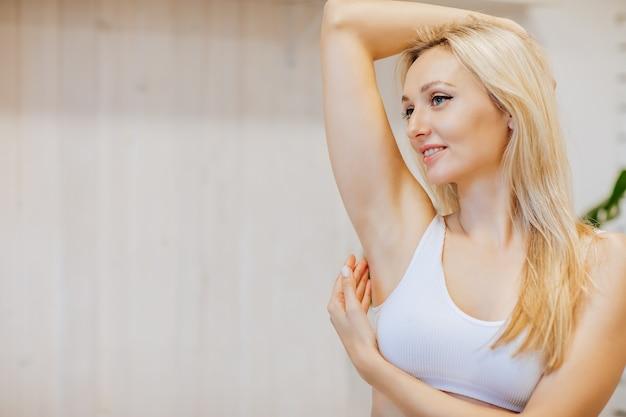 Giovane donna attraente bionda che mostra la sua ascella e il suo sorriso perfetti. concetto di depilazione. copia spazio.