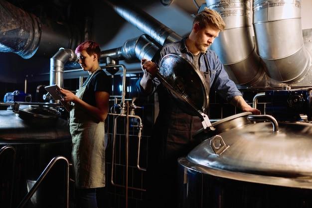 Giovane birraio maschio barbuto biondo in abbigliamento da lavoro che apre il coperchio di un enorme serbatoio di acciaio per la preparazione della birra mentre si lavora con una collega