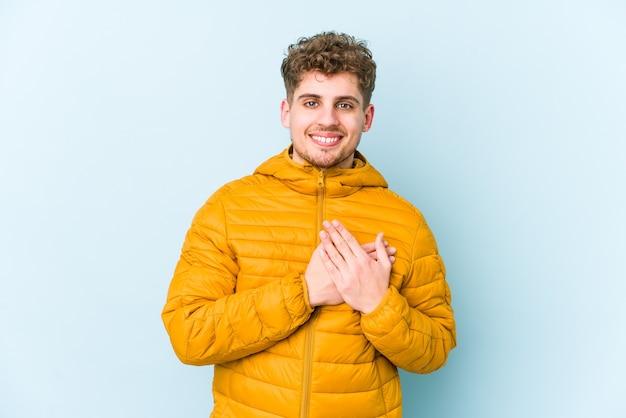 L'uomo caucasico dei giovani capelli ricci biondi isolato ha un'espressione amichevole, premendo il palmo al petto. concetto di amore.