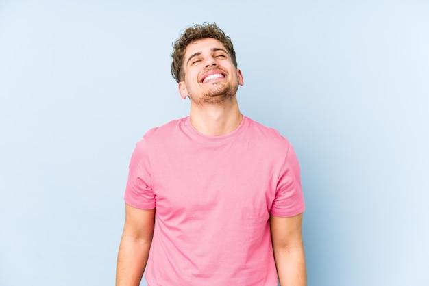 L'uomo caucasico dei giovani capelli ricci biondi ha isolato la risata rilassata e felice, collo allungato che mostra i denti.
