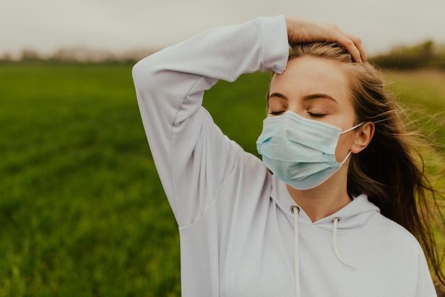 Giovane donna europea bionda in una maschera protettiva all'aperto.