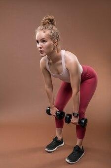 Giovane atleta femminile biondo in activewear piegandosi leggermente in avanti con le gambe piegate sulle ginocchia mentre si sollevano i manubri durante l'allenamento
