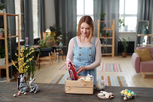 Giovane donna bionda che mette una bottiglia di bevanda alla frutta per bambini e altri spuntini in una scatola di legno mentre si sta in piedi accanto al tavolo in soggiorno