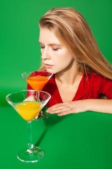Giovane donna bionda con gli occhi chiusi che giace vicino a bicchieri con cocktail colorati durante la festa su sfondo verde